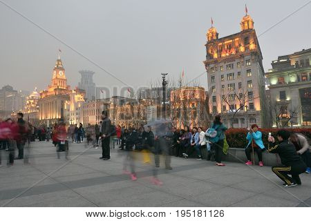 SHANGHAI CHINA - MARCH 18: Unidentified people in a The Bund on March 18 2016 in Shanghai China. The Bund or Waitan is a waterfront area in central Shanghai