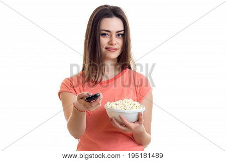 pretty young woman with pop-corn watching a tv isolated on white background