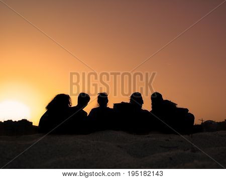 Sunset at the beach with friends. Summer day at the beach. Silhouettes at the beach.