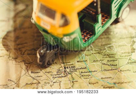 Toy model of auto rickshaw vehicle driving on India map with many cities and the capital in Delhi