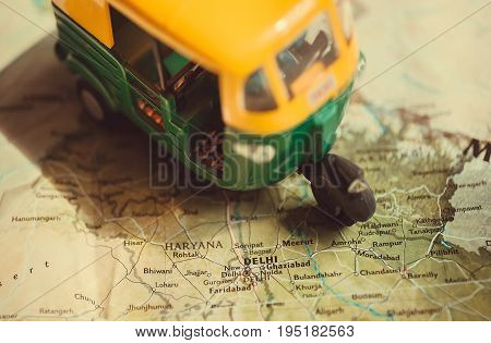 India map with the capital in Delhi and driving toy model of auto-rickshaw vehicle