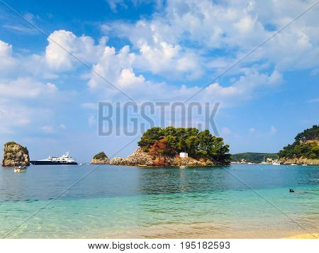Summer vacation background with turquoise sea water bay, yachts and pine trees in Parga, Greece
