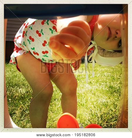 Filtered image of a toddler girl in a bathing suit reaching through the opening of a play house