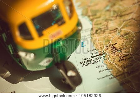 Mumbai city on Indian map with driving toy model of traditional auto-rickshaw vehicle. Symbols of old India.