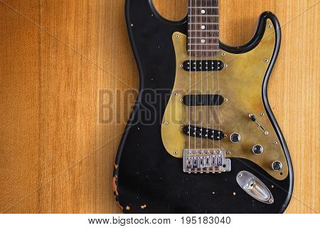 A black custom electric guitar on a wood background
