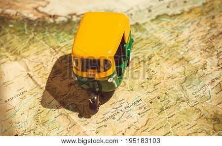 State Madhya Pradesh and Rajasthan on Indian roads map with driving toy model of traditional auto-rickshaw vehicle. Symbols of old India.