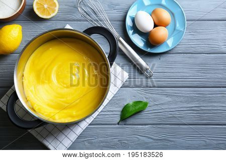 Composition with delicious lemon curd and ingredients on wooden table