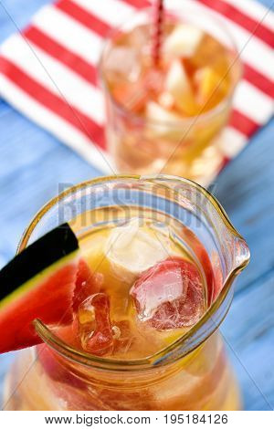 closeup of a pitcher and a glass with refreshing spanish sangria blanca, white sangria, with pieces of fresh fruit, on a rustic blue wooden table