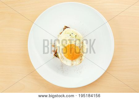 Plate with delicious sunny side up egg and bread slice on wooden background