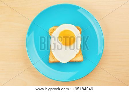 Plate with delicious sunny side up egg and toast on wooden background