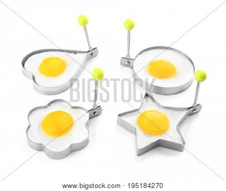 Fried sunny side up eggs in molds of different shapes isolated on white