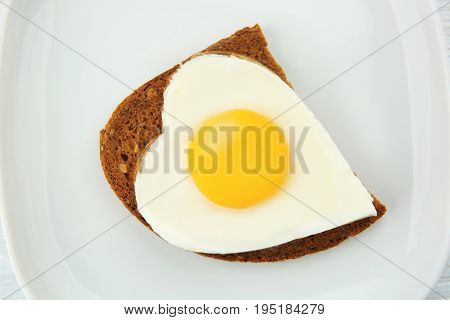 Plate with delicious sunny side up egg and bread slice, closeup