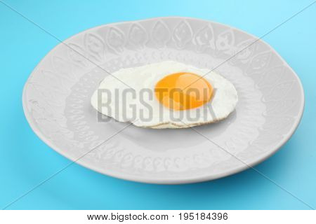 Plate with delicious sunny side up egg on color background