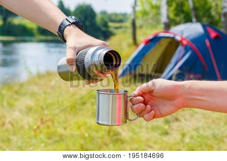 Tea Is Poured Into A Mug At The Camp .