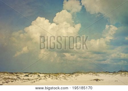 Toned and artistically grunge textured vintage style landscape of puffy cumulus clouds over sand dunes and sea oats.