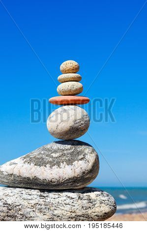 Stones balance on a background of blue sky and summer sea. Concept of balance and harmony