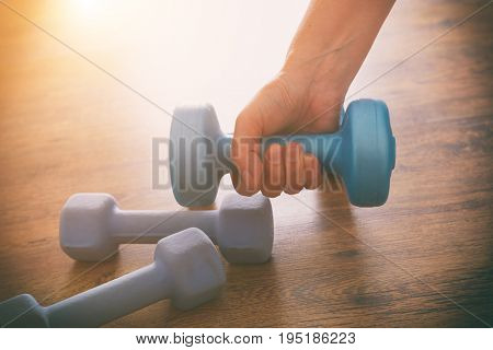 Hand with blue dumb-bells  over wooden floor