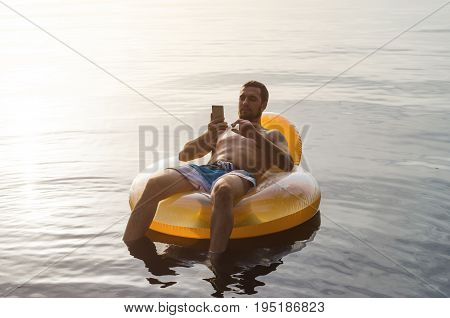 A Man Siting On An Inflatable Ring In The Water And Holding A Smartphone. Young Man Relaxing In A Ru