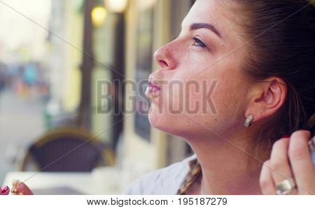 Close up Portrait of young woman eating cookie against city street