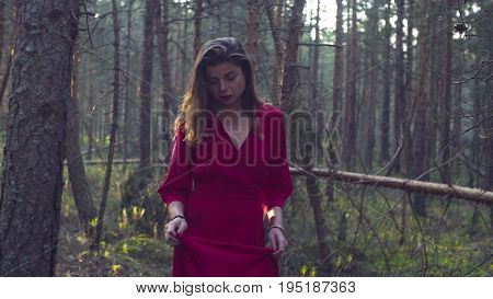 Dolly shot of young beautiful woman in a long red dress walking in the forest