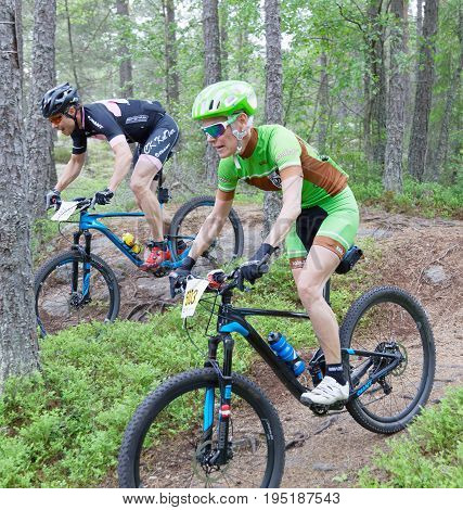 STOCKHOLM SWEDEN - JUNE 11 2017: Side view of two mountain bike cyclists in the forest at Lida Loop Mountain bike Race. June 11 2017 in Stockholm Sweden
