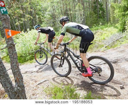 STOCKHOLM SWEDEN - JUNE 11 2017: Side view of group of mountain bike cyclists in the forest at Lida Loop Mountain bike Race. June 11 2017 in Stockholm Sweden