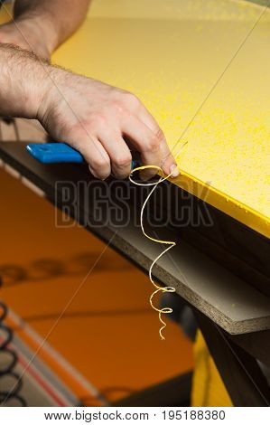 A professional carpenter processes the plastic edges of the countertop with a knife-edge cut. The concept of furniture production