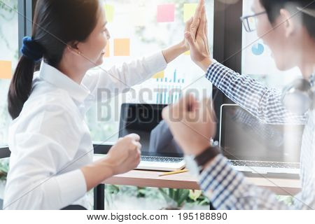 Cheerful Coworkers High Fiving In Creative Office