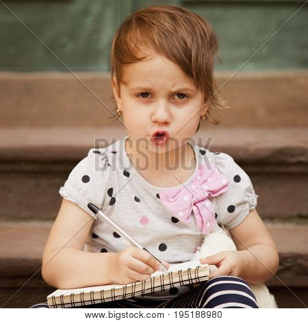 Serious little business child girl writes in notebook and planning her workday. Humorous picture. Time management business job offer analytics research concept.