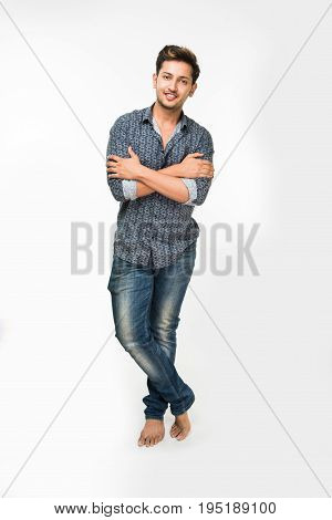 Portrait of good looking Indian or asian young man in casual dressing with folded hands against background
