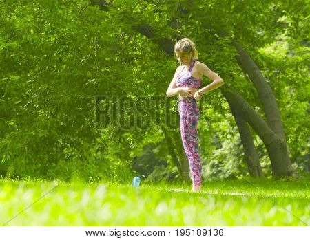 Young woman doing yoga exercises in the park. Surya namaskar