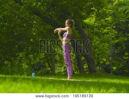 Young attractive woman doing yoga exercises in the park. Utthita hasta padangusthasana