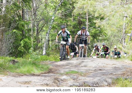 STOCKHOLM SWEDEN - JUNE 11 2017: Group of female and male mountain bike cyclists in the forest at Lida Loop Mountain bike Race. June 11 2017 in Stockholm Sweden