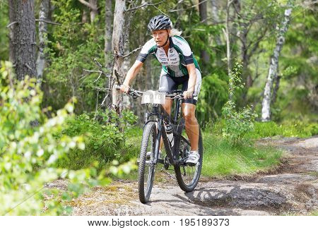 STOCKHOLM SWEDEN - JUNE 11 2017: Female mountain bike cyclist in the forest at Lida Loop Mountain bike Race. June 11 2017 in Stockholm Sweden