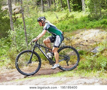 STOCKHOLM SWEDEN - JUNE 11 2017: Side view of female mountain bike cyclist in the forest on a rock at Lida Loop Mountain bike Race. June 11 2017 in Stockholm Sweden