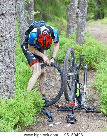 STOCKHOLM SWEDEN - JUNE 11 2017: Mountain bike cyclist fixing a flat tire in the forest at Lida Loop Mountain bike Race. June 11 2017 in Stockholm Sweden