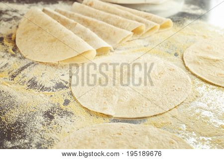 Yummy unleavened tortillas on metal kitchen table