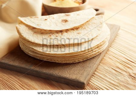 Board with stack of yummy tortillas on wooden table