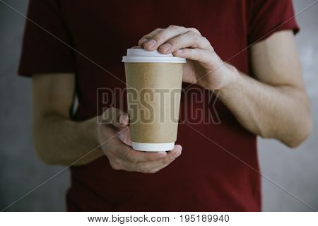 Male hands holding white paper coffee cup to take away.Mock up of clean carton coffee cup.Horizontal mockup, shurt background