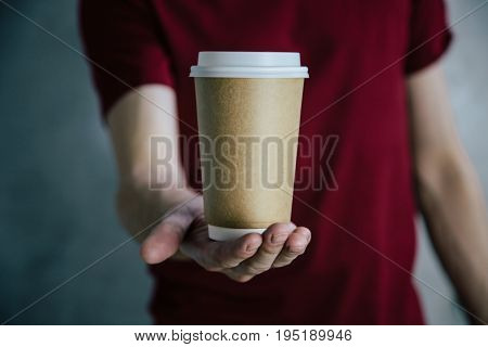 Hand holding a paper coffee cup to take away on red shirt background. Mock up, perfect for putting your design on.