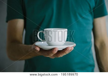 Man's hand holding coffee cup on a green t-shirt background in the studio, advertising coffee. Breakfast and coffee theme