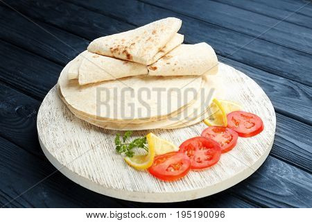 Round board with yummy tortillas and sliced tomato on wooden table