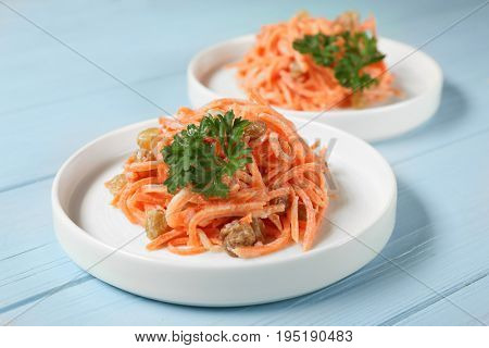 White plates with yummy carrot raisin salad on blue wooden table