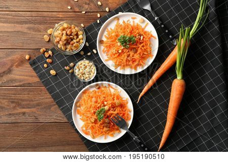 White plates with yummy carrot raisin salad with pine nuts on black checkered napkin, top view
