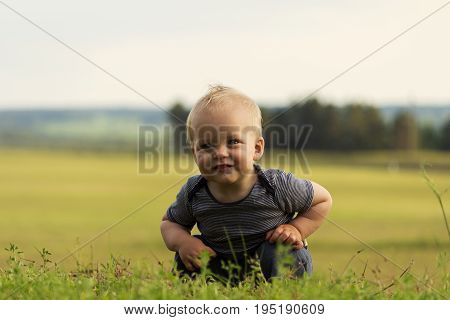 Funny cute toddler squats in the middle of green field.
