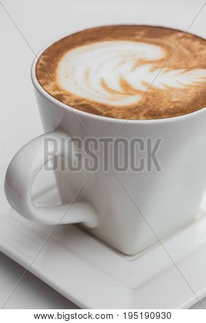 Close up white coffee Coffee cup. latte art on wood table at cafe.