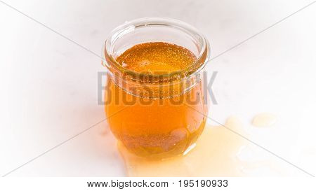 A jar of honey that looks as if someone just poured from it and some has spilled down the sides.