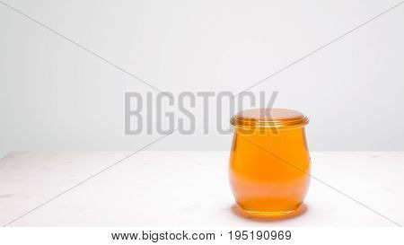 A jar of honey filled to the brim with copy space to the left. Life is full and sweet!