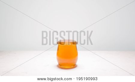 A jar of honey filled to the brim centered on a white marble counter with copy space on both sides. Life is full and sweet!