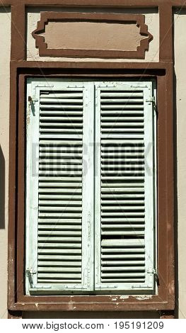 Old wooden shutters on old window. Closed vintage shutters.